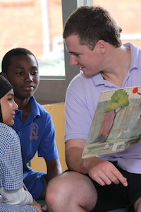 Adult volunteer reading to children